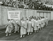 Sacred Heart Cecilians Kitchener Girls in Procession at the Marian Day Celebrations at Ivor Wynne Stadium, then known as Civic Stadium, Photo Credit: Bochsler Studios Ltd, (DHA.001.573)