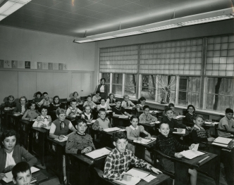 Classroom at St. Joseph Catholic Elementary School, Hamilton with the teacher looking on. [195-? ], Photo Credit: Joseph Bochsler Photography, (DHA.001.592)
