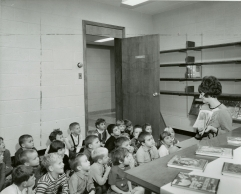 Black and white photographic portrait of teacher Joan Moore, reading to her class in the library at the then newly built St. Michael Catholic Elementary School, Hamilton, ON, 1966, Photo Credit: The Canadian Register, (DHA.001.615)